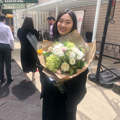 Award winner Maggie Chen holding a bouquet of flowers.